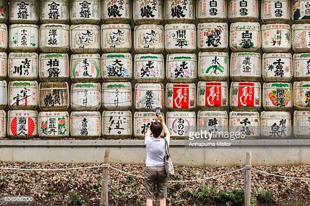 A woman photographs a wall of Sake Casks at the Meiji-Jingu Shrine in Tokyo, Japan