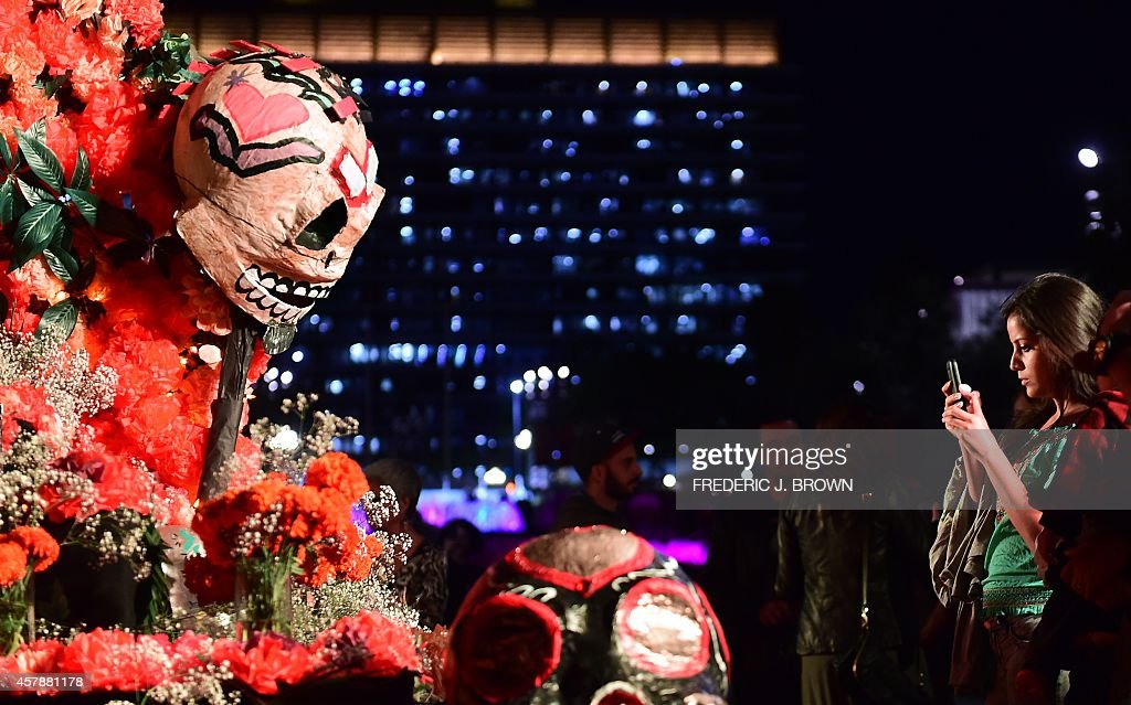 A woman photographs an altar display during a traditional Mexican celebration of 'Noche de Ofrenda' in downtown Los Angeles California on October 25...