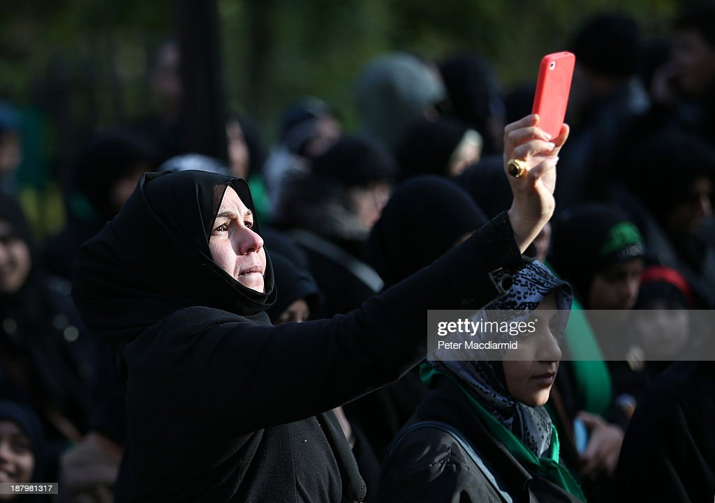 A woman photographs an Ashura day mourning procession on her mobile phone on November 14, 2013 in London, England. Ashura is a day of solemn mourning for the martyrdom of Hussein in 680 AD.