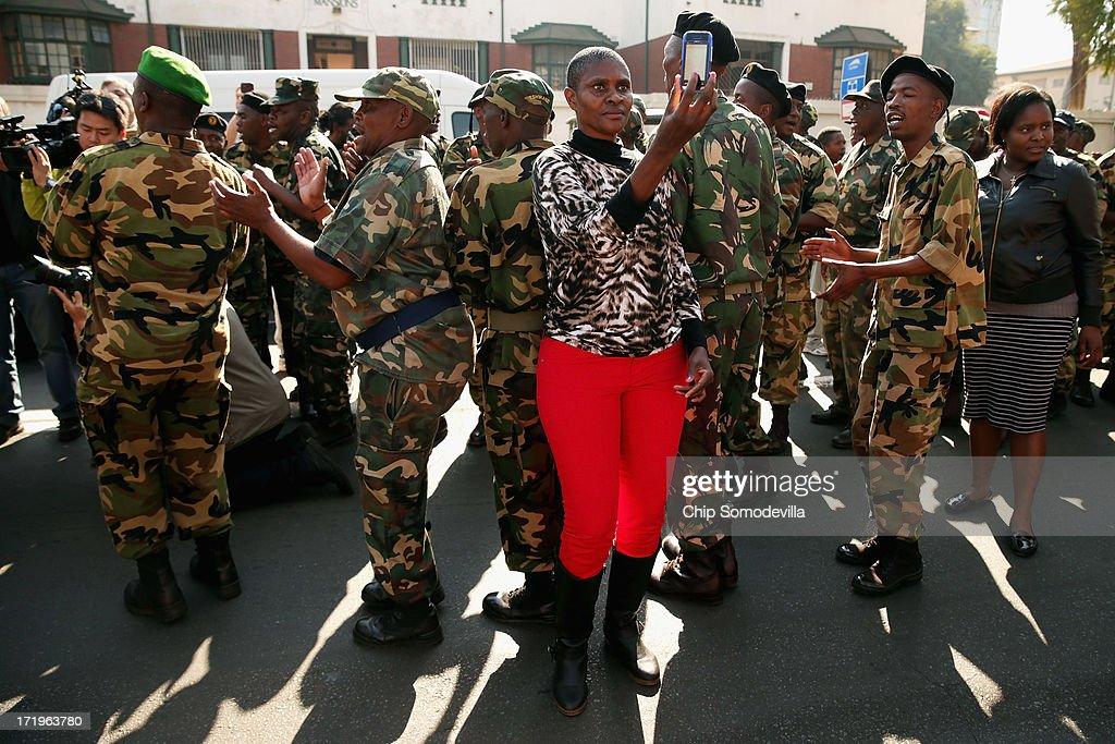 A woman photographs herself with members of the Umkhonto We Sizwe Military Veterans Association outside the Mediclinic Heart Hospital where former South African President Nelson Mandela is being treated for a recurring lung infection June 30, 2013 in Pretoria, South Africa. The anti-apartheid icon and Nobel Peace Prize laureate has been in the hospital for three weeks where his condition has been described as 'critical but stable.'