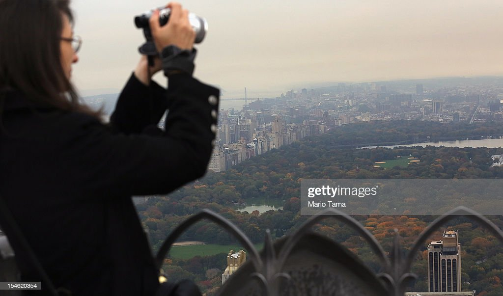 A woman photographs Manhattan and Central Park from the 'Top of the Rock' observation deck at Rockefeller Center on October 23 2012 in New York City...