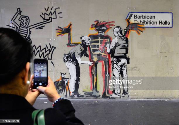A woman photographs street art created in September 2017 near the Barbican Centre in London England by Banksy an anonymous Englandbased graffiti...