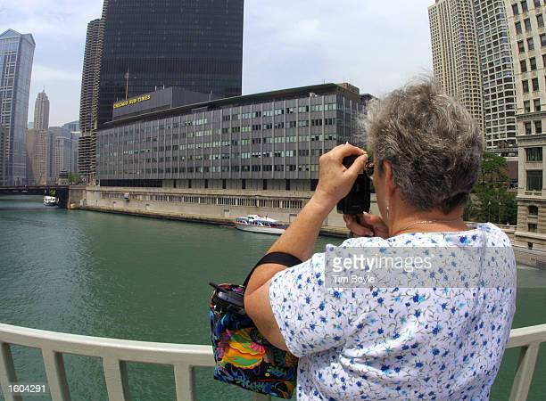 A woman photographs the Chicago River July 25 2001 with the Chicago SunTimes building right visible in downtown Chicago Donald Trump and the owners...