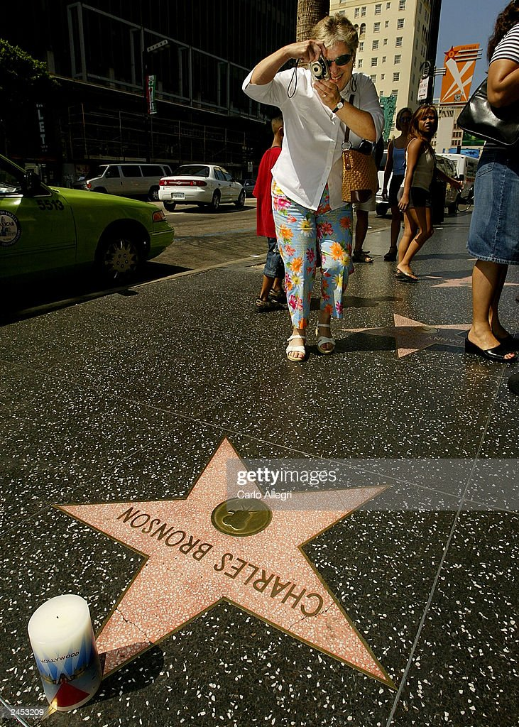 A woman photographs the star of actor Charles Bronson on the Hollywood Walk of Fame September 1, 2003 in Hollywood, California. Bronson died of pneumonia at the age of 81 August 30, 2003 in Los Angeles, California.