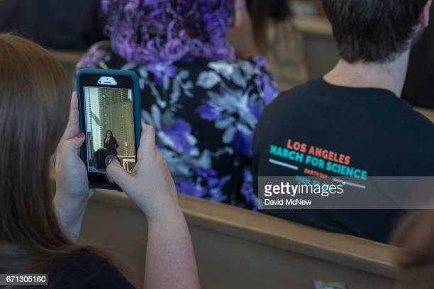 A woman photographs US Senator Kamala D Harris as a man wear a Los Angeles March for Science shirt which will be held tomorrow during a town hall at...