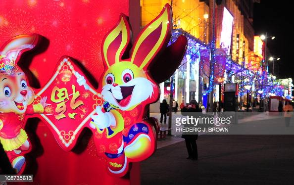 A woman photographs 'Year of the Rabbit' decorations on Wangfujing Street in Beijing on January 29 2011 Beside twelve animals and the twelveyear...