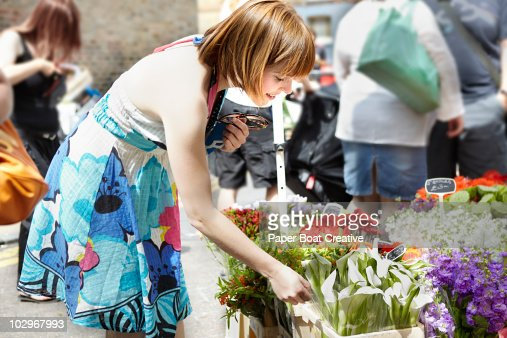 Woman picking flowers from the local market : Stock Photo