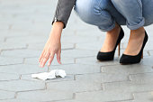 Close up of a woman hand picking garbage of the sidewalk on the street