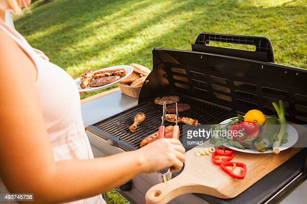 Woman picking meat from barbecue.