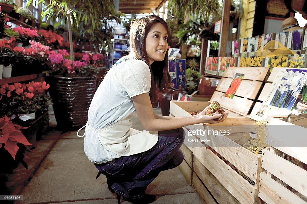 Woman picking out bulbs at a plant nursery : Stock Photo