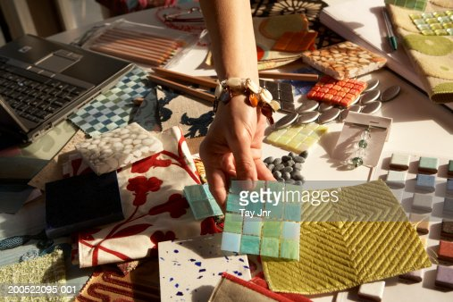 Woman picking out swatches from desk : 스톡 사진