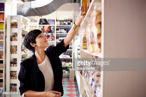 Woman picking up bottle of juice at grocery store