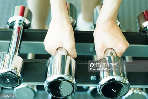Woman picking up dumbbells