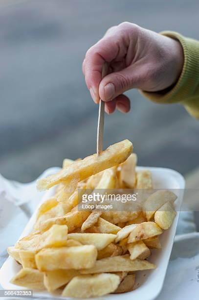 A woman picking up fried potato chip with a wooden fork