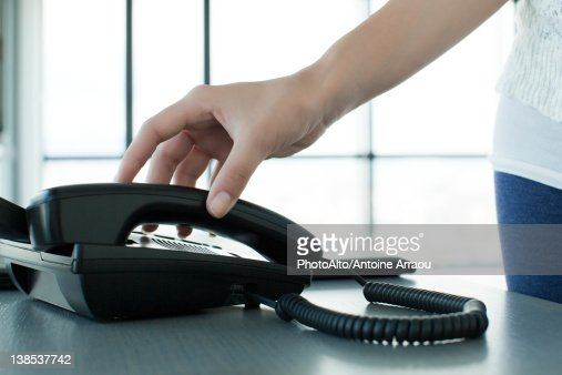 Woman picking up telephone receiver, backlit, cropped