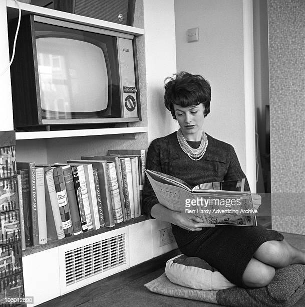 A woman picks a book from her shelf 13th February 1961 She is professional model June Bryant