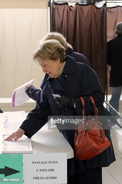 A woman picks ballot papers prior to casting her vote during the first round of the French municipal elections at a polling station set in...