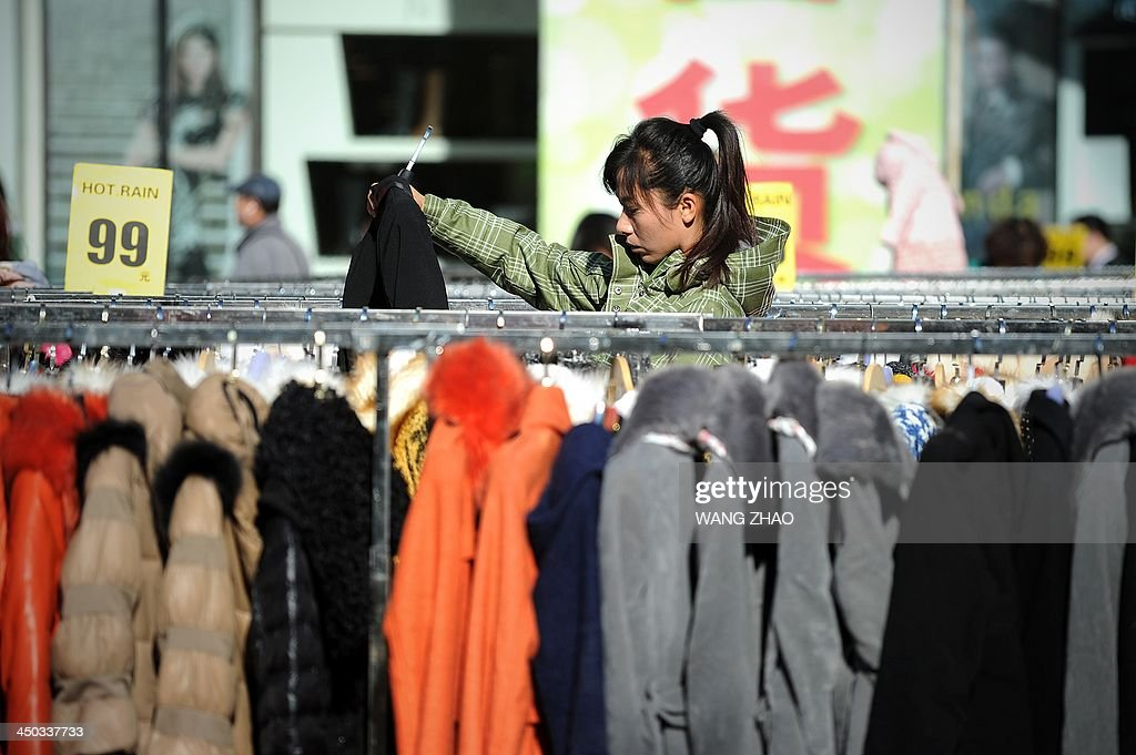 A woman picks out clothes during a sales promotion outside a mall in Beijing on November 18, 2013. China's quick release of a surprisingly detailed national reform plan shows leaders are serious about economic change, analysts say, but uncertainties remain over its implementation. AFP PHOTO / WANG ZHAO