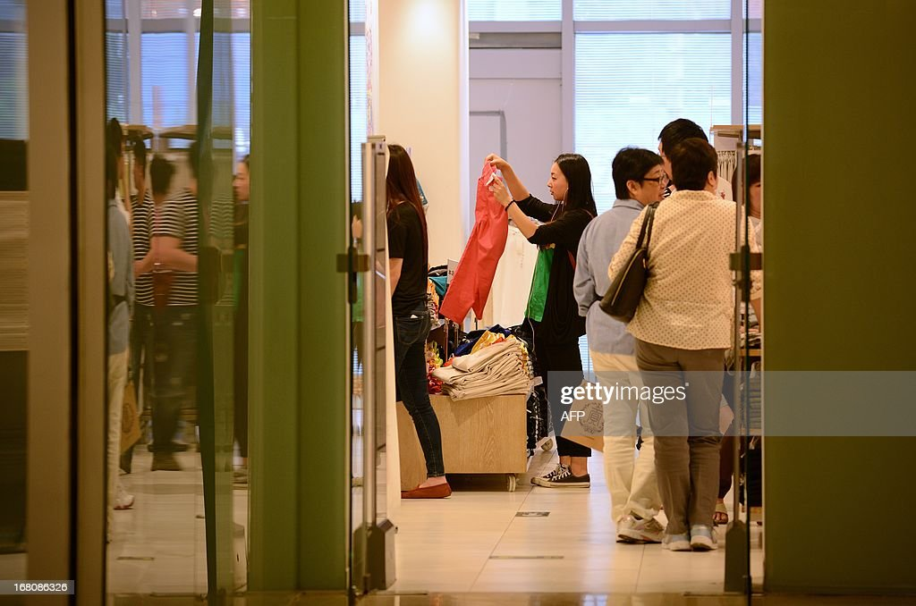 A woman (C) picks out clothes while shopping at a store in Beijing on May 5, 2013. Manufacturing activity in China slowed slightly in April from the previous month, official data showed on May 1, in a sign of further weakness in the world's second-biggest economy.