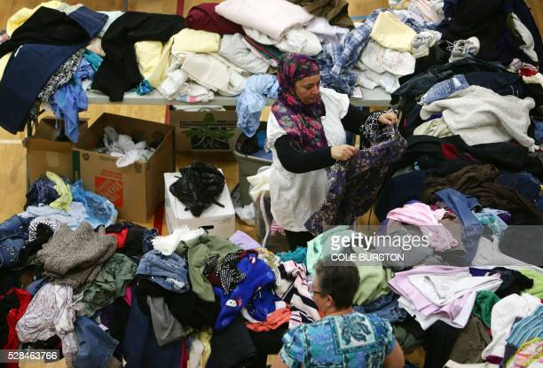 A woman picks through donated clothing and goods at a makeshift evacuee center in Lac la Biche Alberta on May 5 after fleeing forest fires north of...
