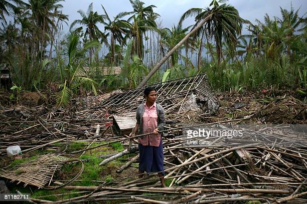 A woman picks through the wreckage of her home at the isolated village of Myasein Kan on May 20 2008 in the Ayeyarwaddy delta Myanmar It has been...