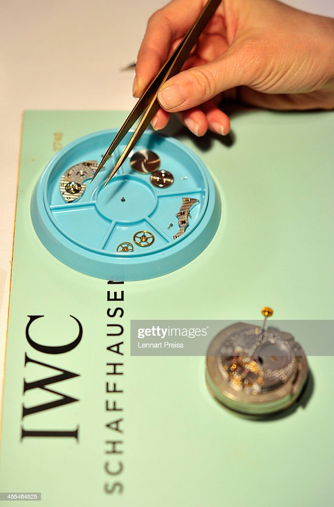 A woman picks up a piece of a clockwork with a pair of tweezers during a watchmaking class by swiss watch manufacturer IWC at The Charles Hotel on December 12, 2013 in Munich, Germany.