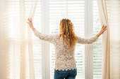 Woman looking out big bright window with curtains and blinds