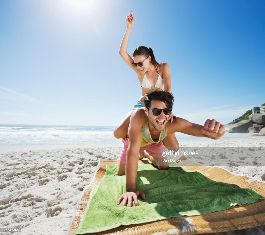 Woman piggybacking enthusiastic man on beach : Stock Photo