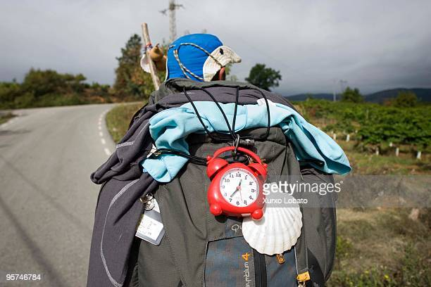 A woman pilgrim walks with a backpack and a clock and shell in a Bierzo region in the way of saint James in Castilla and Leon 10th November 2009