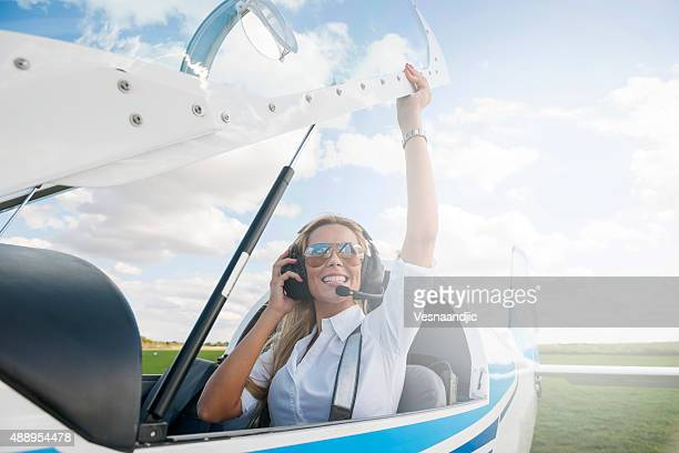 Woman pilot looking at camera, preparing for flying