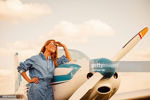 Woman  pilot looking at sky, preparing for flying