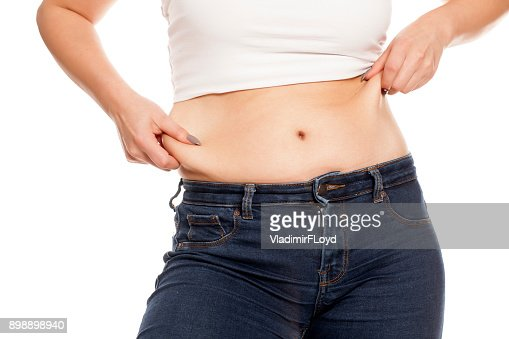 woman pinches her fat on her belly : Stock Photo