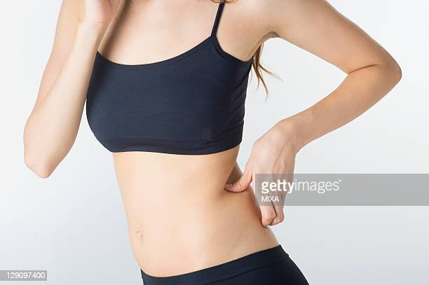 Woman Pinching Fat on Side of Waist