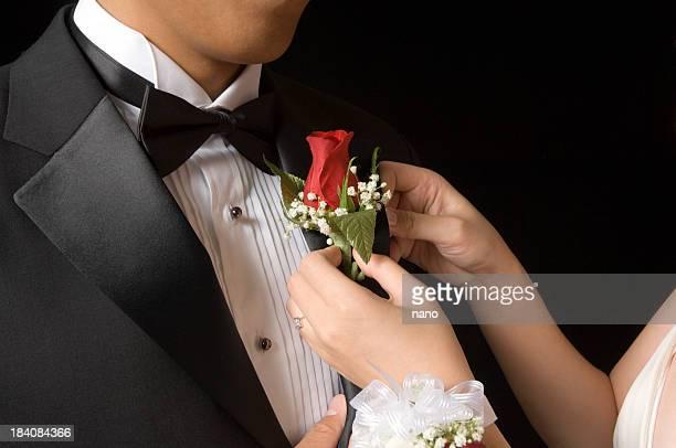 Woman pinning boutonniere on man's lapel