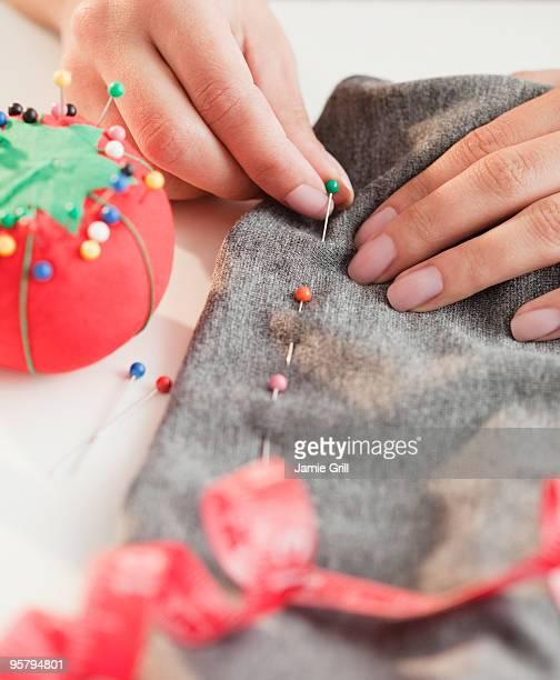 Woman pinning dress hem, close up