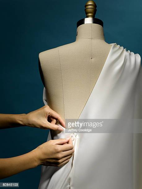 Woman pinning material on dress form
