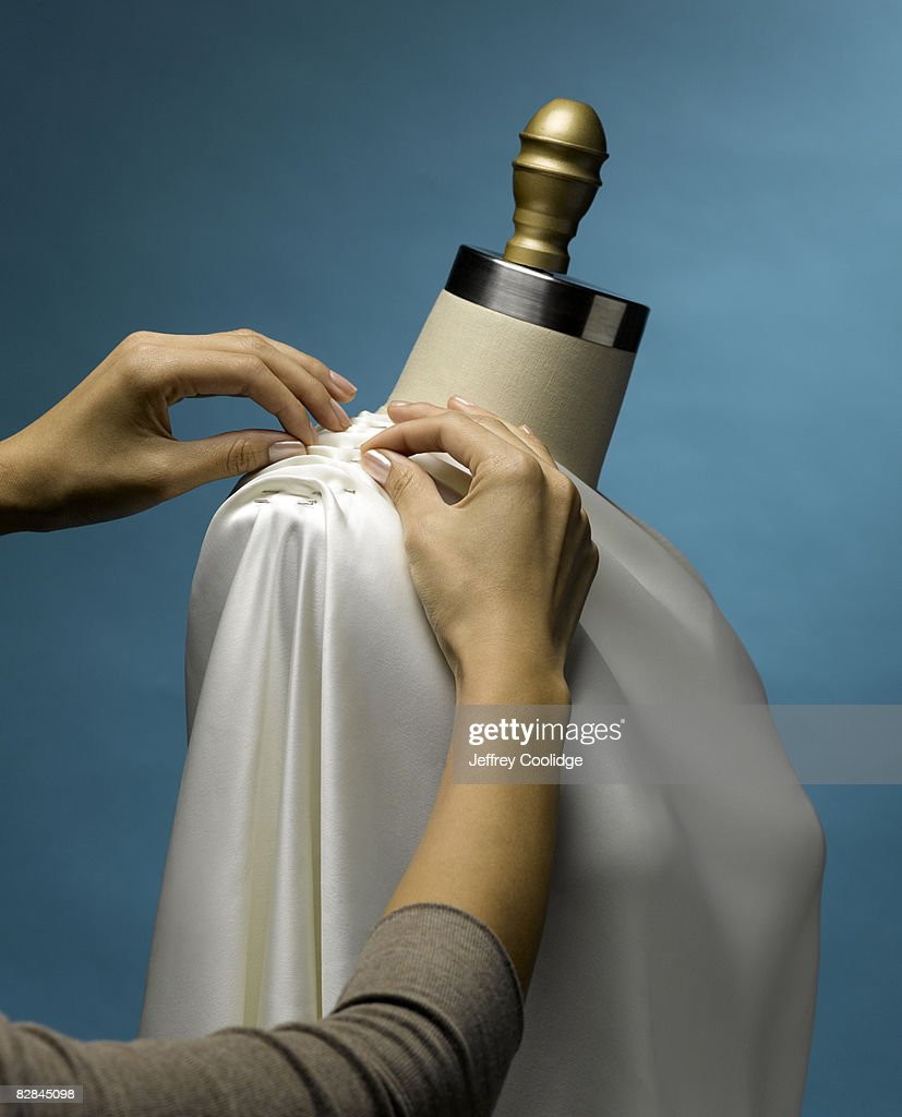 Woman pinning material on dress material : Stock Photo
