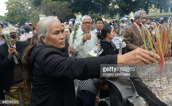A woman place incenses sticks during a small rally marking the 38th anniversary of the Chinese war border against Vietnam in front the statue of...