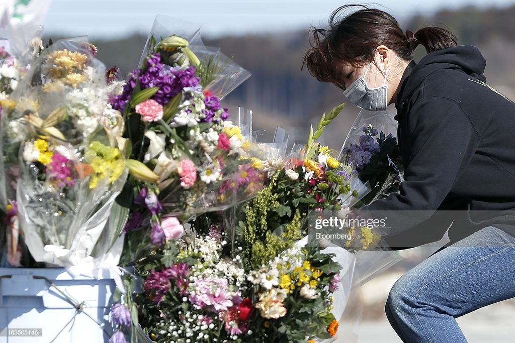 A woman places a bouquet of flowers in front of the remaining structure of a former disaster center, unseen, to commemorate the second anniversary of the Great East Japan Earthquake and Tsunami in Minamisanriku, Miyagi Prefecture, Japan, on Monday, March 11, 2013. Two years after a record earthquake devastated Japan's northeast, Prime Minister Shinzo Abe has driven the nation's bond risk to levels from before the disaster with a plan that will add to the world's biggest debt burden. Photographer: Kiyoshi Ota/Bloomberg via Getty Images