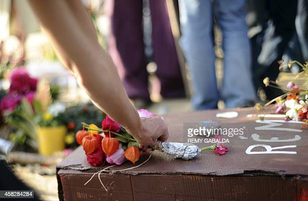 A woman places a bunch of flowers on a cardboard replica coffin as some 300 people take part in a march in memory of Remi Fraisse a 21yearold...