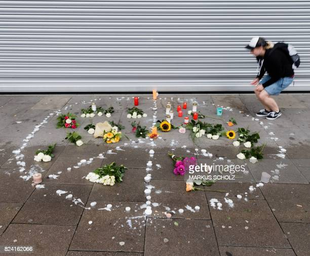 A woman places a candle at a makeshift memorial of flowers and candles arranged like a peace sign on July 29 2017 in Hamburg northern Germany at the...