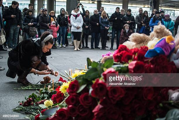 A woman places a candle at a memorial for the victims of Airbus A321 crash at the Pulkovo Airport on November 1 2015 in St Petersburg Russia A...