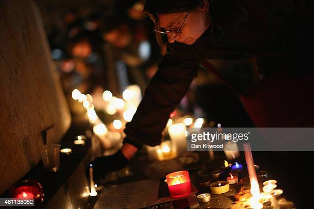 A woman places a candle at a vigil at the Place de la Republique for victims of the terrorist attack on January 7 2015 in Paris France Twelve people...