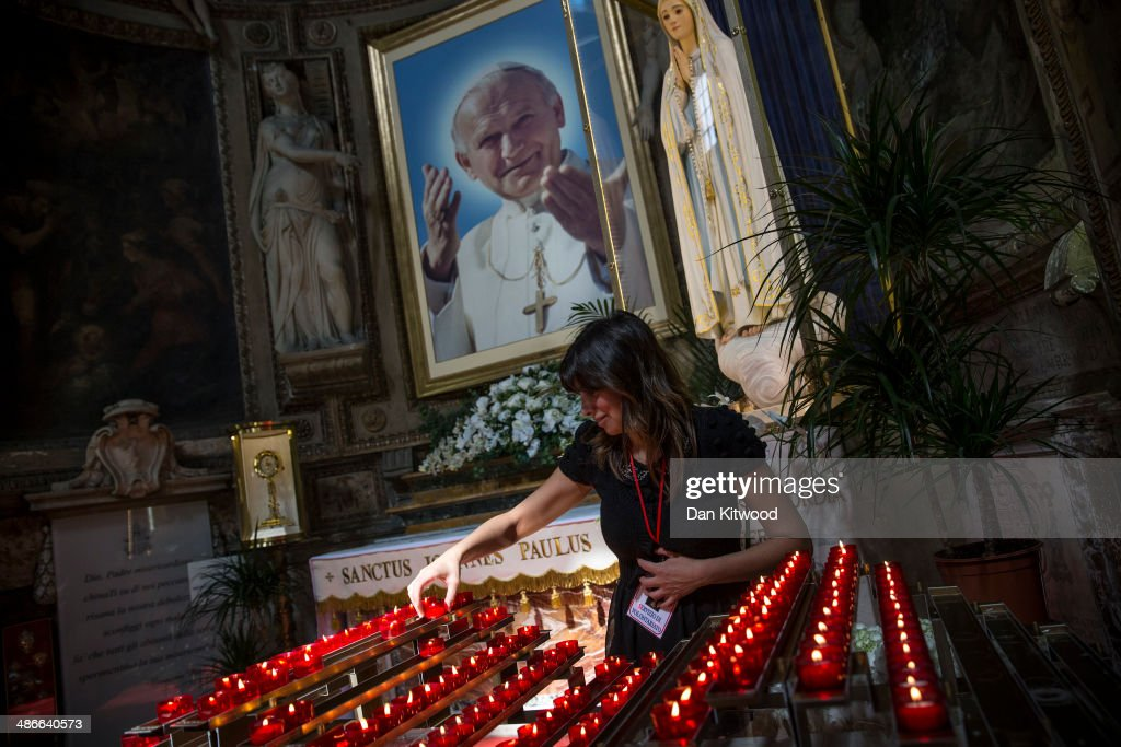 A woman places a candle during a mass at the Polish Church, Santo Spirito in Sassia, Sanctuary of Divine Mercy on April 25, 2014 in Rome, Italy. The late Pope John Paul II and Pope John XXIII will be canonised on Sunday 27 April, inside the Vatican when 800,000 pilgrims from around the world are expected to attend.