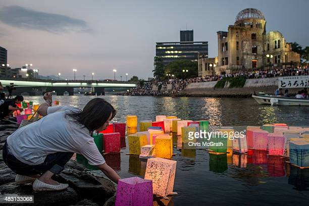 A woman places a candle lit paper lantern on the river during 70th anniversary activities commemorating the atomic bombing of Hiroshima at the...