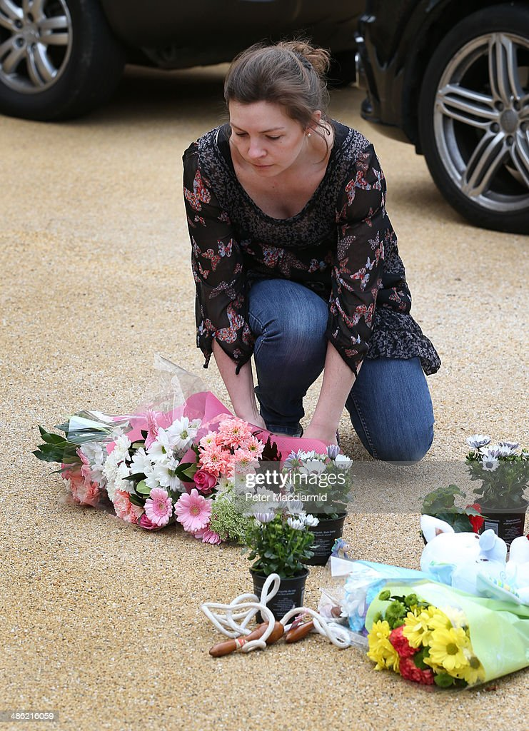 A woman places a floral tribute on the drive of a house in New Malden on April 23, 2014 in south London, England. Police say that a 43 year old woman has been arrested after the bodies of three children were found at a property last night.