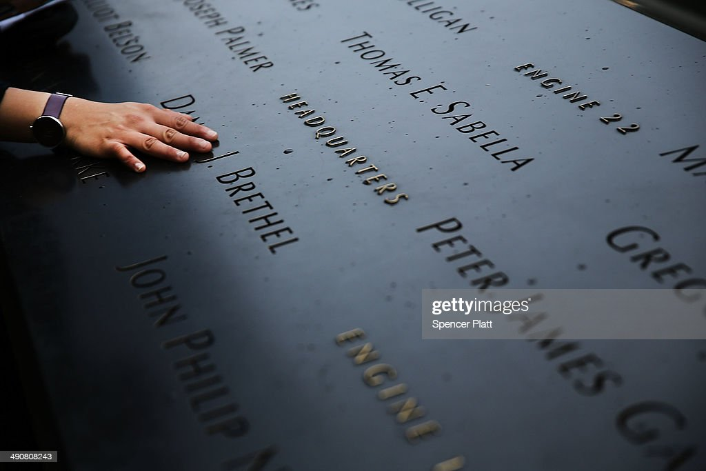 A woman places a hand on the names engraved along the South reflecting pool at the Ground Zero memorial site during the dedication ceremony of the National September 11 Memorial Museum in New York May 15, 2014 in New York City. The museum spans seven stories, mostly underground, and contains artifacts from the attack on the World Trade Center Towers on September 11, 2001 that include the 80 ft high tridents, the so-called 'Ground Zero Cross,' the destroyed remains of Company 21's New York Fire Department Engine as well as smaller items such as letter that fell from a hijacked plane and posters of missing loved ones projected onto the wall of the museum. The museum will open to the public on May 21.