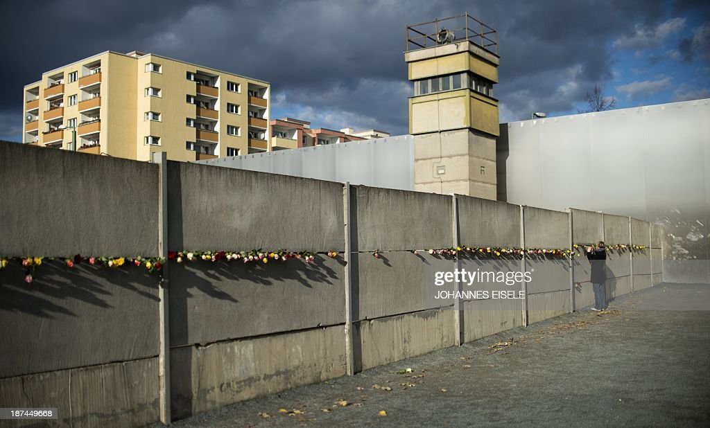 A woman places a rose in a preserved segment of the Berlin Wall memorial at Bernauer Strasse on November 9, 2013 in Berlin on occasion of the 24th anniversary of the fall of the Wall.