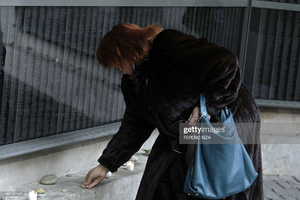 A woman places a stone next to the wall of victims at the Holocaust Museum in Budapest, Hungary on January 27, 2013, the International Holocaust Memorial Day to commemorate the victims of the Nazi regime.