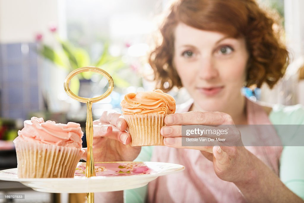 Woman places cupcake on cake plate. : Stock Photo